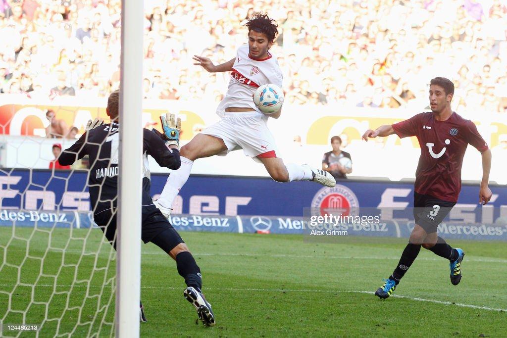Serdar Tasci of Stuttgart scores his team's third goal against goalkeeper RonRobert Zieler and Karim Haggui of Hannover during the Bundesliga match...