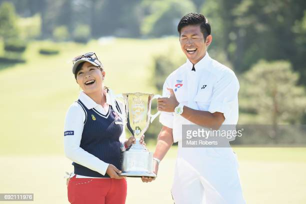 Serena Aoki of Japan poses for a photo with the winners trophy and her caddie during the final round of the Yonex Ladies Golf Tournament 2016 at the...