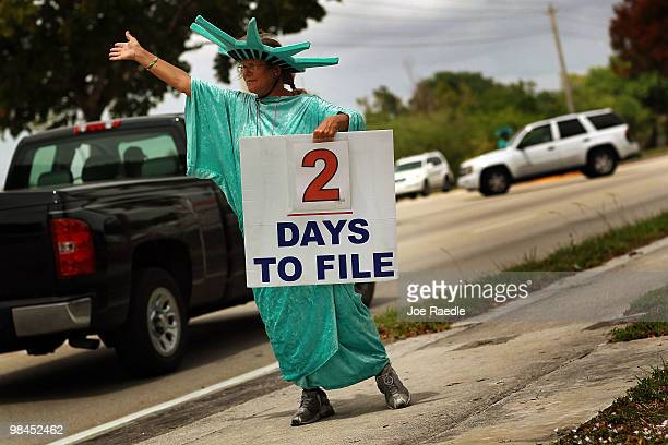 Serena Watson holds a sign advertising a tax preparation office for people that still need help completing their taxes before the Internal Revenue...