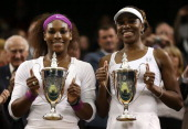 Serena Williams and Venus Williams of the USA pose with their winners trophies after winning their Ladies' Doubles final match against Andrea...