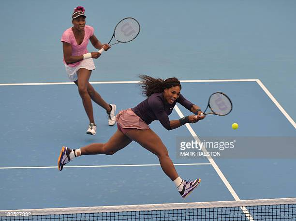 Serena Williams chases a backhand shot watched by her sister Venus during their women's doubles match against Chan Haoching of Tiawan and Liezel...