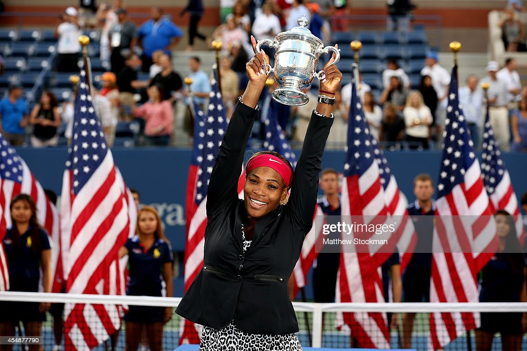 Serena Williams of the United States celebrates with the trophy after defeating Caroline Wozniacki of Denmark to win their women's singles final...