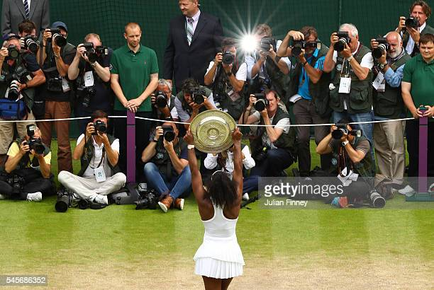 Serena Williams of The United States lifts the trophy infront of the photogrpahers following victory in The Ladies Singles Final against Angelique...