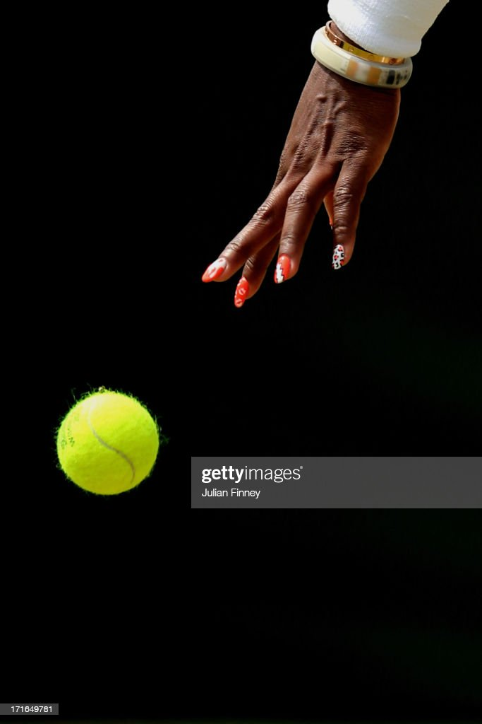 Serena Williams of the United States of America bounces a tennis ball as she prepares to serve during the Ladies' Singles second round match against Caroline Garcia of France on day four of the Wimbledon Lawn Tennis Championships at the All England Lawn Tennis and Croquet Club on June 27, 2013 in London, England.