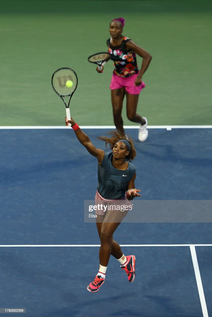 Serena Williams of the United States of America smashes the balll in front of her partner Venus Williams of the United States of America during their women's doubles first round match against Silvia Soler Espinosa of Spain and Carla Suarez Navarro of Spain on Day Four of the 2013 US Open at USTA Billie Jean King National Tennis Center on August 29, 2013 in the Flushing neighborhood of the Queens borough of New York City.