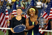 Serena Williams of the United States poses with the championship trophy next to Victoria Azarenka of Belarus following her victory in the women's...