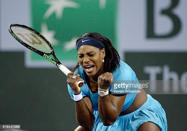 Serena Williams of the United States reacts after breaking Agnieszka Radwanska of Poland serves during the second set tiebreaker during day twelve of...