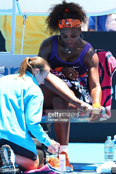 Serena Williams of the United States receives medical attention after falling onto the court injuring her ankle in her first round match against...