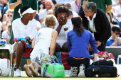 Serena Williams of the United States recieves treatment during the warm up before their Ladies Doubles second round match with Venus Williams against...