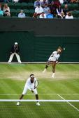 Serena Williams of the United States serves during her Ladies Doubles first round match with Venus Williams against Oksana Kalashnikova of Georgia...