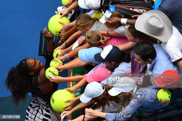 Serena Williams of the United States signs autographs for fans after winning her first round match against Belinda Bencic of Switzerland on day two...