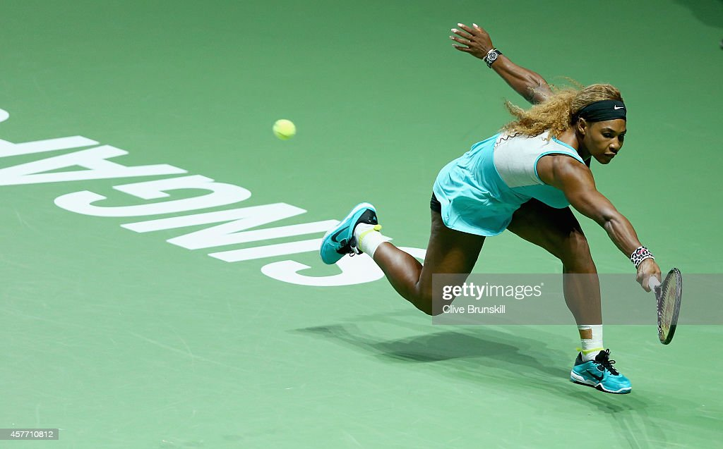 Serena Williams of the United States stretches to play a backhand against Eugenie Bouchard of Canada in their round robin matchduring the BNP Paribas WTA Finals at Singapore Sports Hub on October 23, 2014 in Singapore.