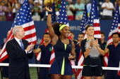 Serena Williams of the United States waves to the crowd before receiving the championship trophy after defeating Victoria Azarenka of Belarus to win...