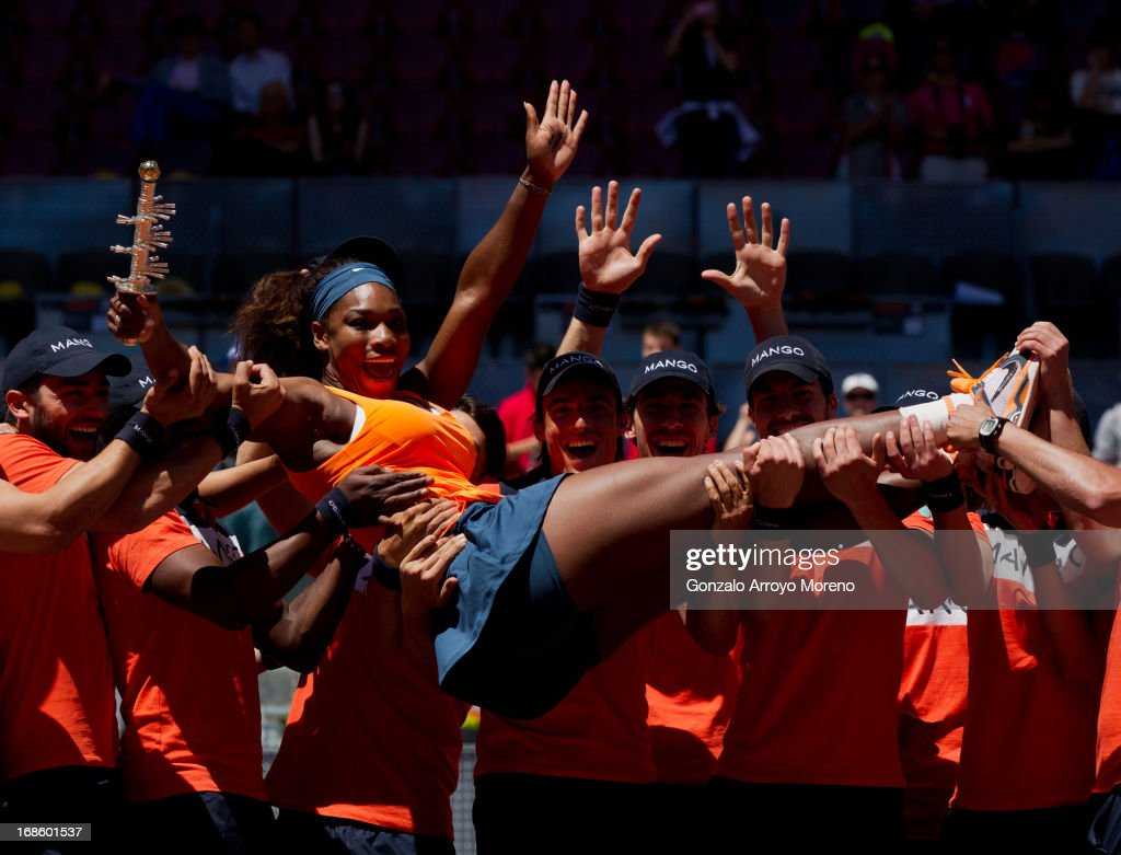 Serena Williams of the US celebrates with ball boys holding on to her trophy after winning her final match against Maria Sharapova of Russia on day nine of the Mutua Madrid Open tennis tournament at the Caja Magica on May 12, 2013 in Madrid, Spain.