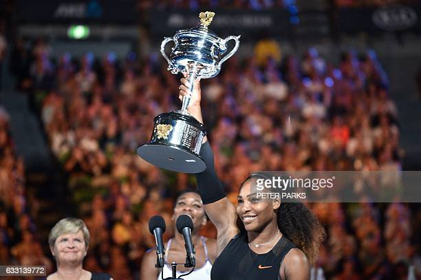 Serena Williams of the US celebrates with the championship trophy during the awards ceremony after her victory against Venus Williams of the US in...
