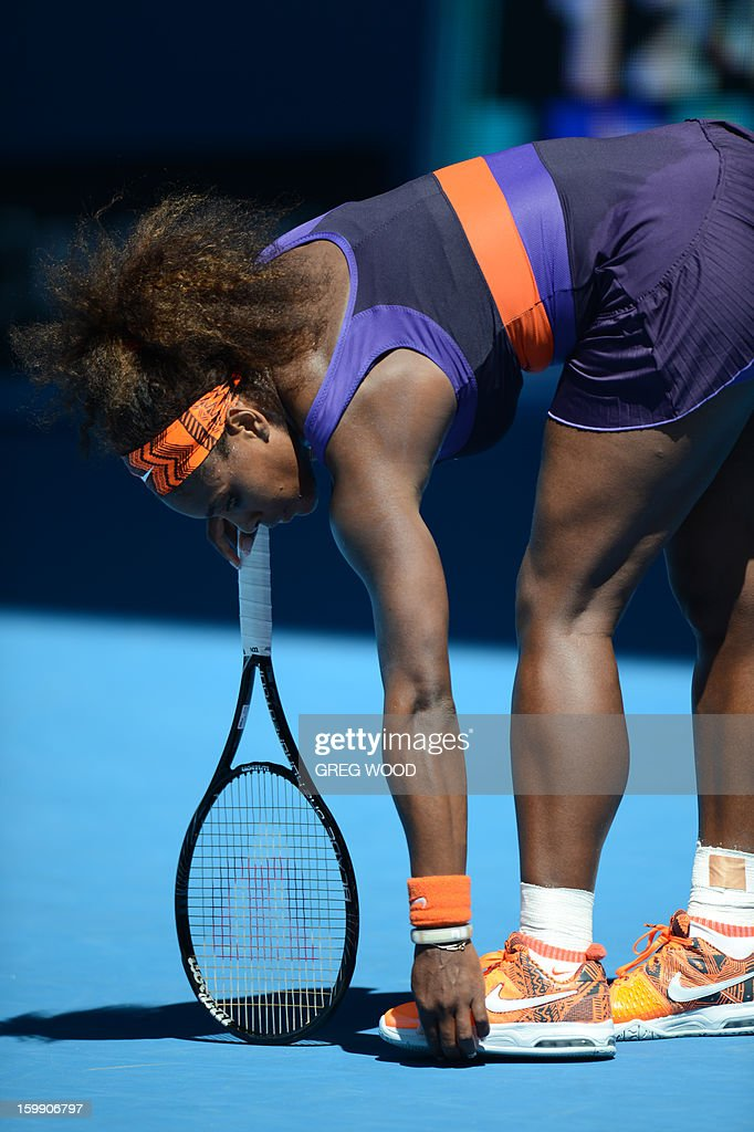 Serena Williams of the US holds her foot during her women's singles match against compatriot Sloane Stephens on the tenth day of the Australian Open tennis tournament in Melbourne on January 23, 2013.