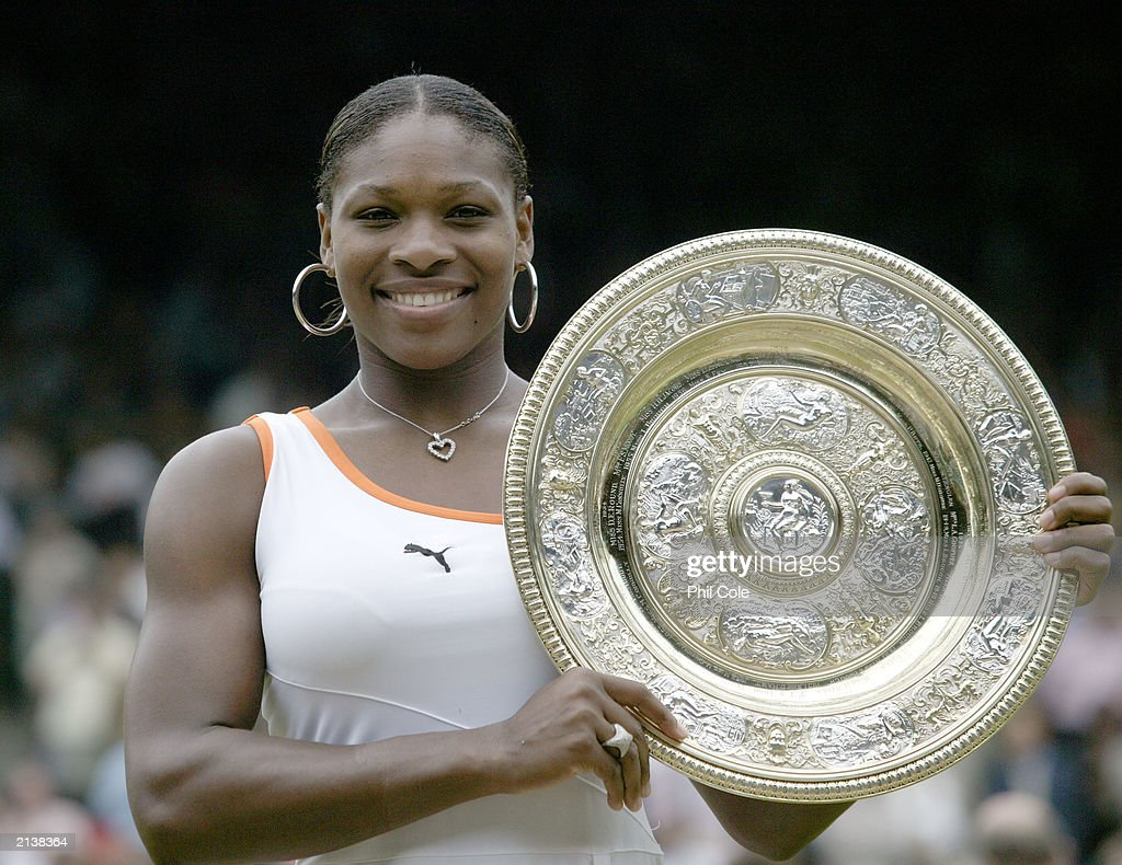 Serena Williams of the US holds her trophy after her victory over Venus Williams in the Womens Singles Final during day twelve of the Wimbledon...