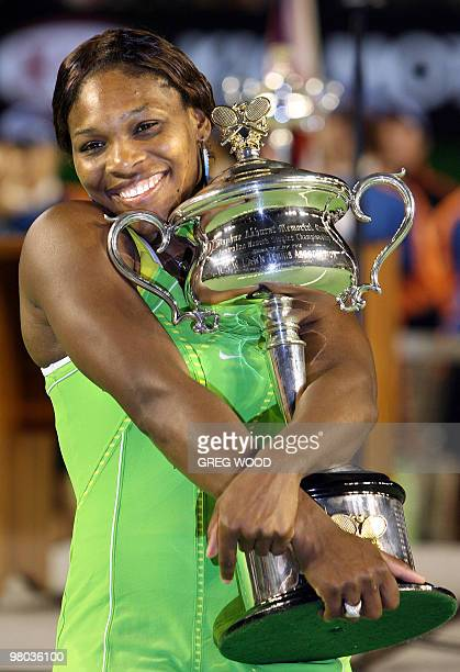 Serena Williams of the US holds the winner's trophy following her victory in the women's singles final match over Maria Sharapova of Russia at the...