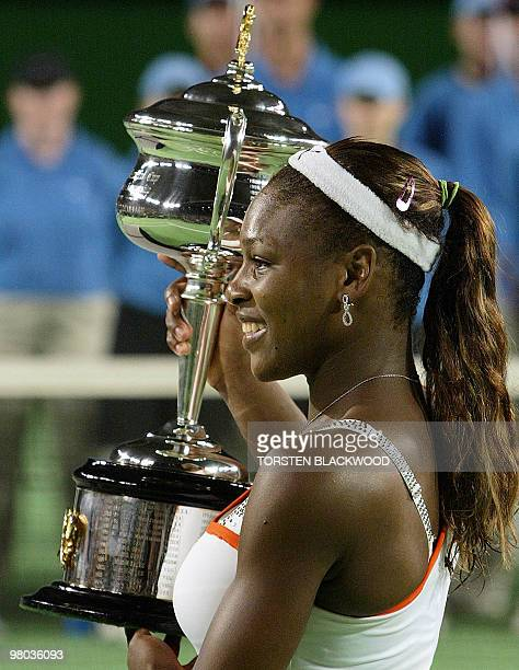 Serena Williams of the US holds the winner's trophy following her victory over her sister Venus in the women's singles final at the Australian Open...