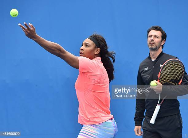 Serena Williams of the US is watched by coach Patrick Mouratoglou as she serves during a practice session ahead of the 2015 Australian Open tennis...