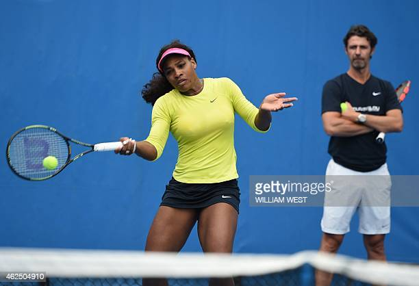 Serena Williams of the US is watched by coach Patrick Mouratoglou as she plays a shot during a training session on day twelve of the 2015 Australian...