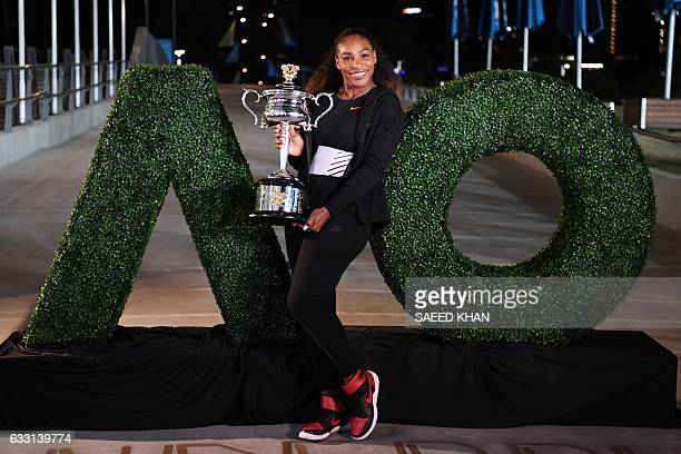 Serena Williams of the US poses with the championship trophy after her victory against Venus Williams of the US in the women's singles final on day...