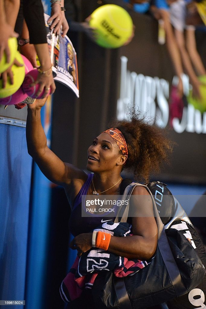 Serena Williams of the US signs autographs after her victory against Russia's Maria Kirilenko during their women's singles match on day eight of the Australian Open tennis tournament in Melbourne on January 21, 2013. AFP PHOTO / PAUL CROCK IMAGE STRICTLY RESTRICTED TO EDITORIAL USE - STRICTLY NO COMMERCIAL USE