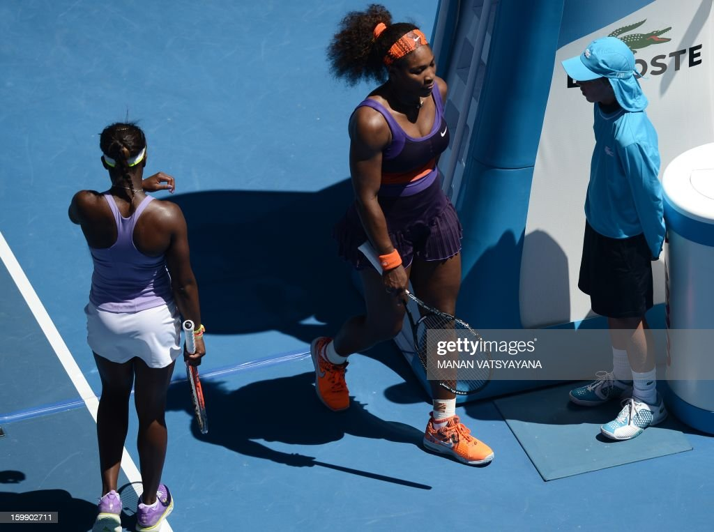 Serena Williams of the US (C) walks past Sloane Stephens of the US (L) during their women's singles match on day ten of the Australian Open tennis tournament in Melbourne on January 23, 2013.