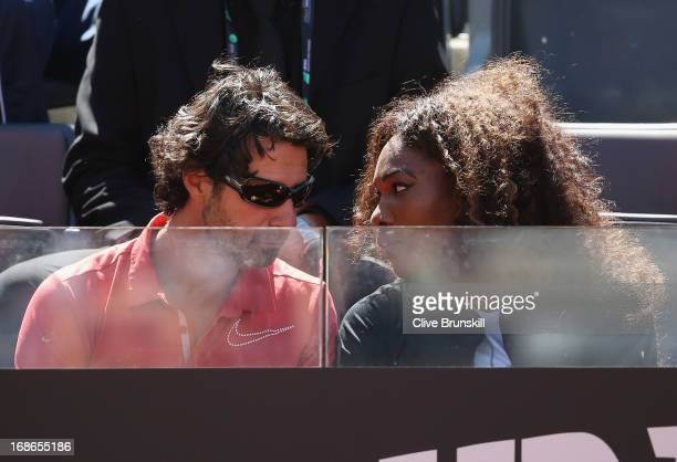 Serena Williams of the USA and her coach Patrick Mourataglou watch her sister Venus Williams of the USA play against Laura Robson of Great Britain in...