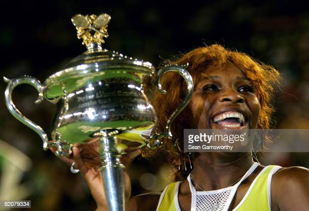 Serena Williams of the USA holds aloft the trophy after winning the Womens Final against Lindsay Davenport of the USA during day thirteen of the...