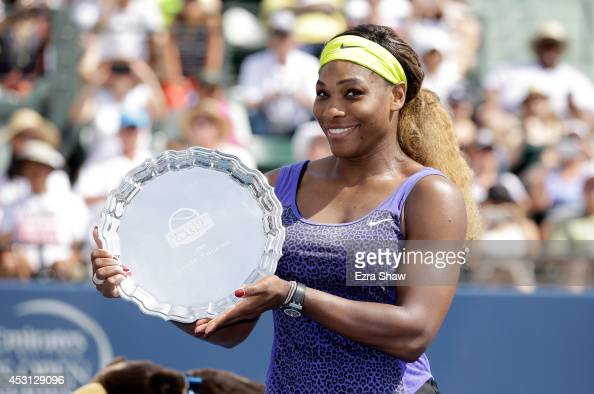 Serena Williams of the USA holds up the trophy after beating Angelique Kerber of Germany in the finals of the Bank of the West Classic at the Taube...