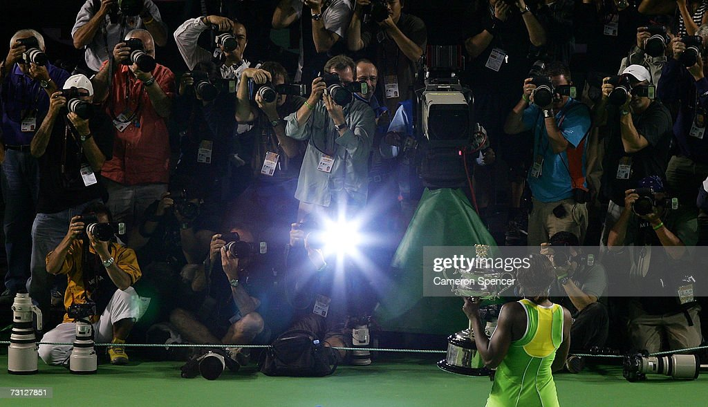 Serena Williams of the USA poses with the trophy after winning her women's final match against Maria Sharapova of Russia on day thirteen of the...