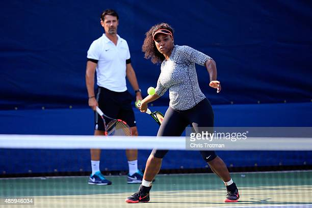 Serena Williams of United States hits a ball during a practice session as her coach Patrick Mouratoglou looks on prior to the US Open at USTA Billie...