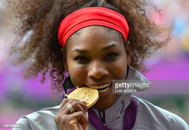 US Serena Williams poses on the podium with her gold medal after defeating Russia's Maria Sharapova in the women's singles gold medal match of the...