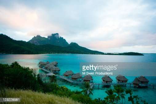 Serene blue resort bungalows over water : Stock Photo