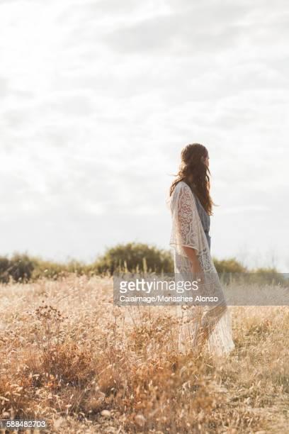 Serene boho woman standing in rural field