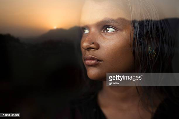 Serene girl looking at sunset view from behind glass window.