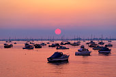 The sun sets ovr Poole Harbour. Boats are silhouetted against the bright sunlight