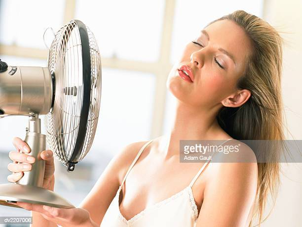Serene Woman Cools Herself With an Electric Fan