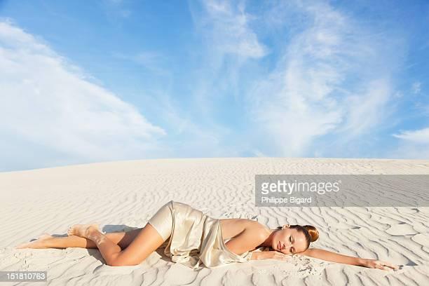 Serene woman laying on white sand beach