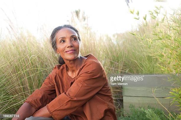 Serena donna seduta in campo di sole