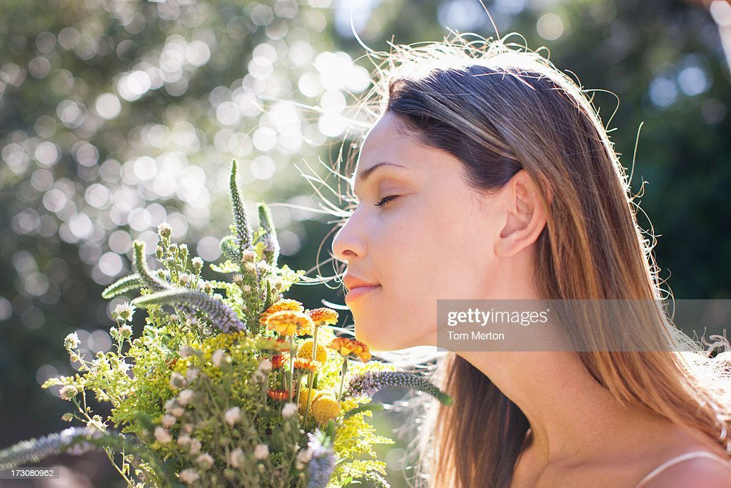 Serene woman smelling bouquet : Stock Photo