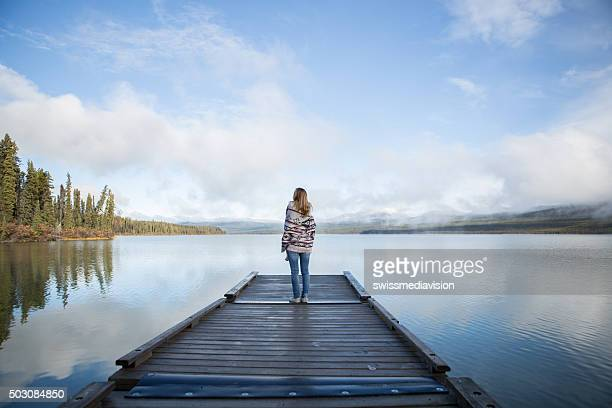 Serene woman stands on pier relaxing by the lake