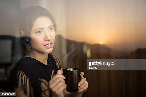 Serene young woman enjoying sunrise view and having coffee break.