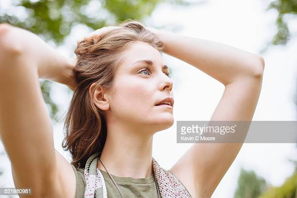 Serene young woman gazing up with hands in hair