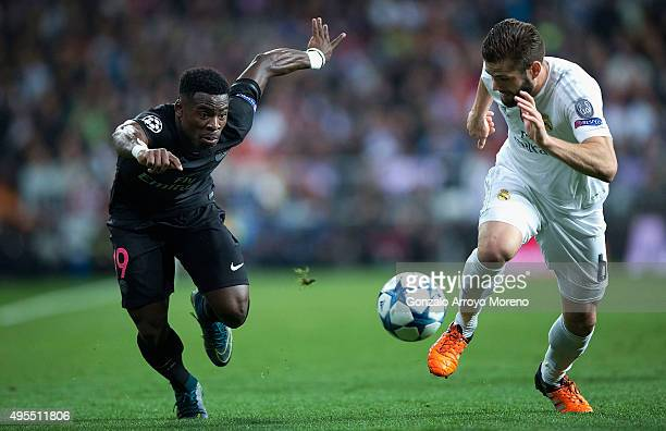 Serge Aurier of PSG and Nacho Fernandez of Real Madrid chase the ball during the UEFA Champions League Group A match between Real Madrid CF and Paris...