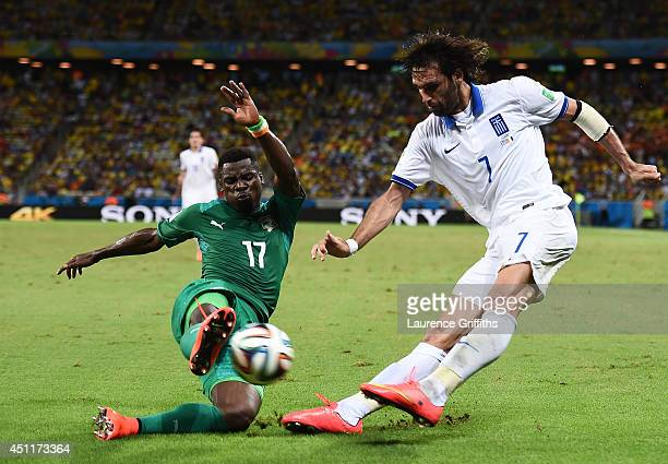 Serge Aurier of the Ivory Coast challenges Giorgos Samaras of Greece during the 2014 FIFA World Cup Brazil Group C match between Greece and the Ivory...