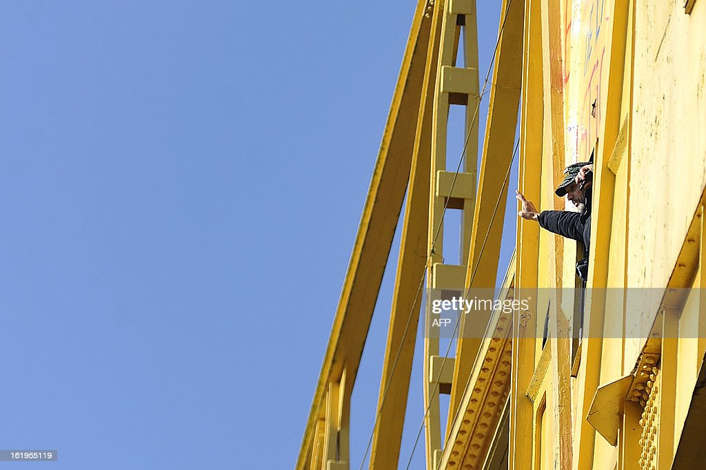 Serge Charnay, a father denied access to his son, gestures as he stands on a 43-meter crane on February 18, 2013 in the western French city of Nantes for a fourth day of a protest for his rights as a father. Charnay has struggled to win back the right to see his son, born in 2006, after losing custody and all visiting rights when he was accused of kidnapping the boy.