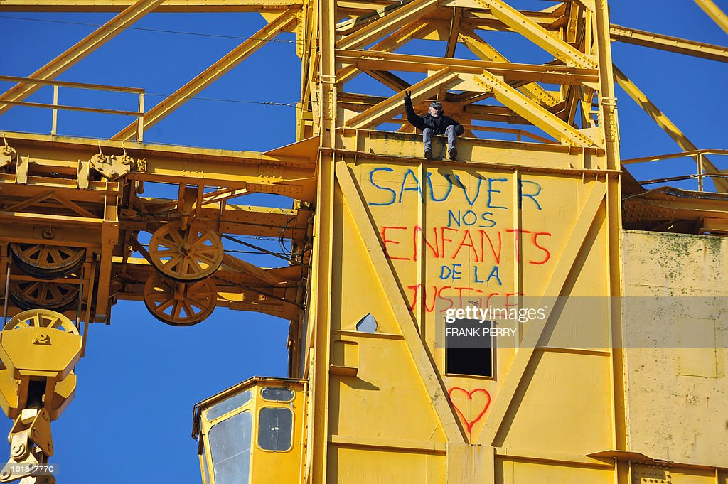 Serge Charnay gestures from a 43-meter crane on February 17, 2013 after spray painting the message ' Save our children from the justice' in Nantes on the third day of a protest for his rights as a father. A second man yesterday climbed another crane in 'an act of solidarity' with Charnay, an action sanctioned by French association 'SOS Papa' indicating that the two men are' victims of family justice in France' .