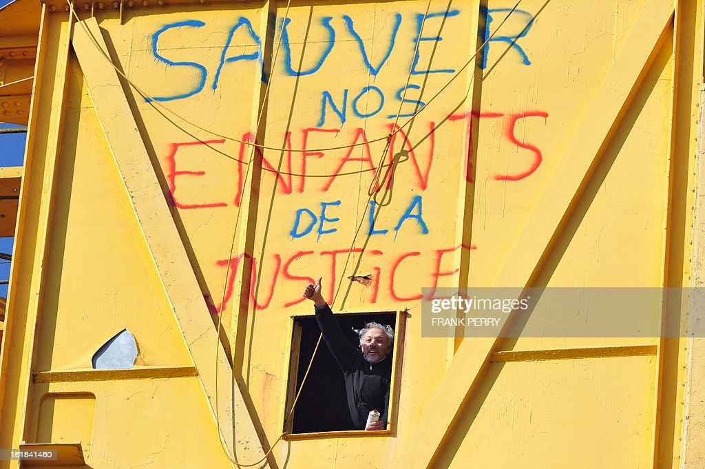 Serge Charnay gives the thumbs up from a 43-meter crane on February 17, 2013 after spray painting the message ' Save out children from the justice' in Nantes on the third day of a protest for his rights as a father. A second man yesterday climbed another crane in 'an act of solidarity' with Charnay, an action sanctioned by French association 'SOS Papa' indicating that the two men are' victims of family justice in France' . AFP PHOTO / FRANK PERRY